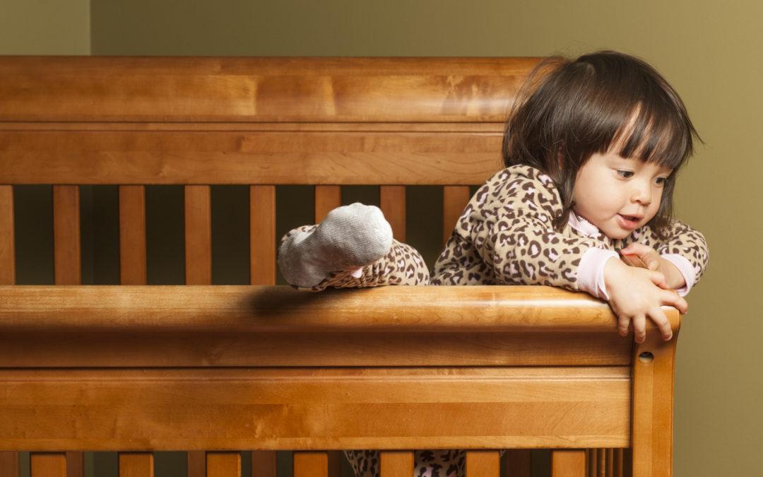 toddler girl climbing out of crib